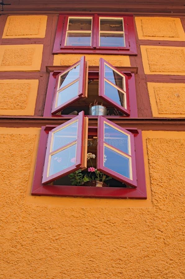 Heldere geeloranje muur van rustiek oud huis met drie vensters en verse bloemen Loket, Tsjechische Republiek royalty-vrije stock foto