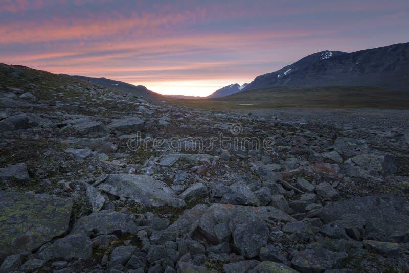 Heldere gekleurde gestreepte zonsondergang over het ruwe rotsachtige Sarek-landschap stock afbeelding