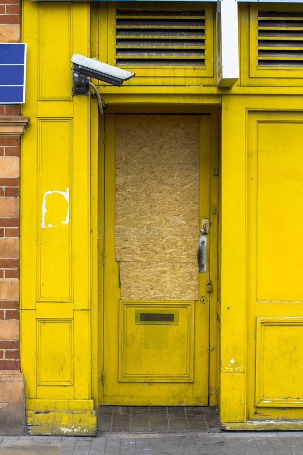 Heldere gele die ingang door een videocamera gecontroleerd Ingang met triplex wordt belemmerd dat De gele deur is gesloten Veilig royalty-vrije stock fotografie