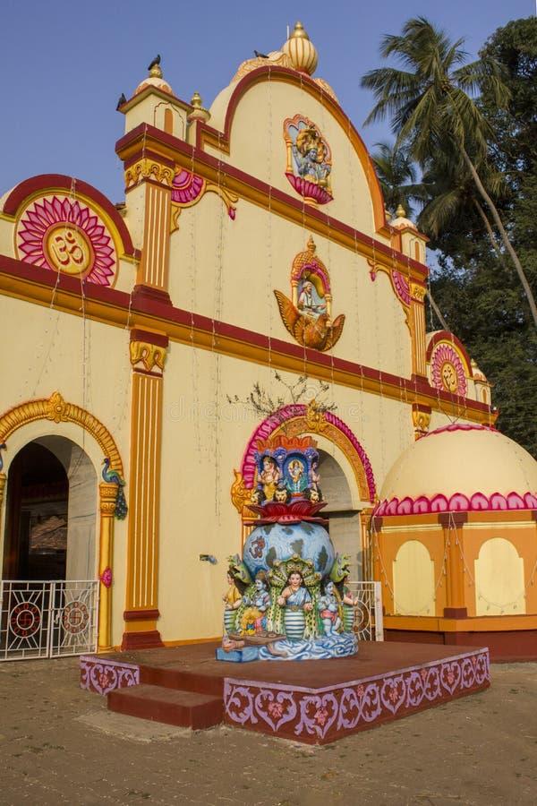 Heldere gele Hindoese tempel met de standbeelden van de goden van mythologie, tegen de achtergrond van groene palmen onder de bla royalty-vrije stock afbeelding