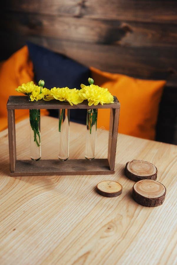 Heldere gele madeliefjes in een glasvaas op houten zwaard stock foto