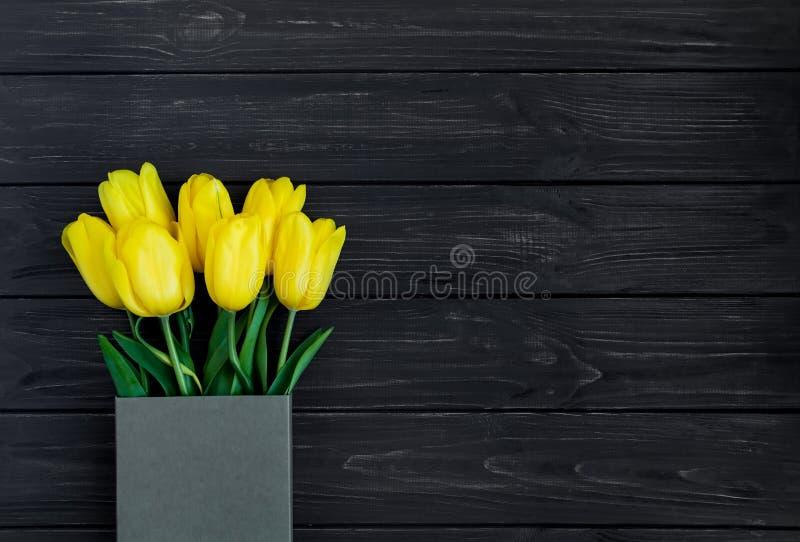 Heldere gele tulpen in ecodocument vakje op zwarte uitstekende houten lijst Vlak leg, hoogste mening royalty-vrije stock afbeelding