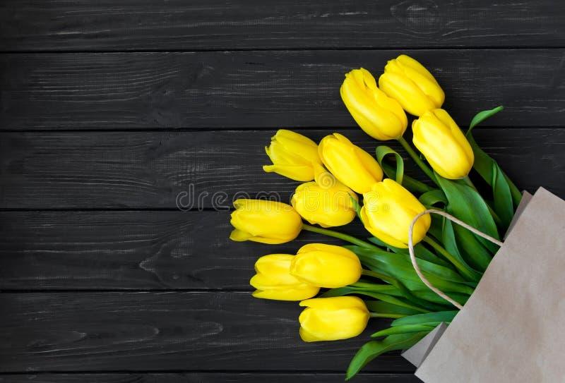 Heldere gele tulpen in ecodocument zak op zwart uitstekend houten Ta royalty-vrije stock afbeeldingen