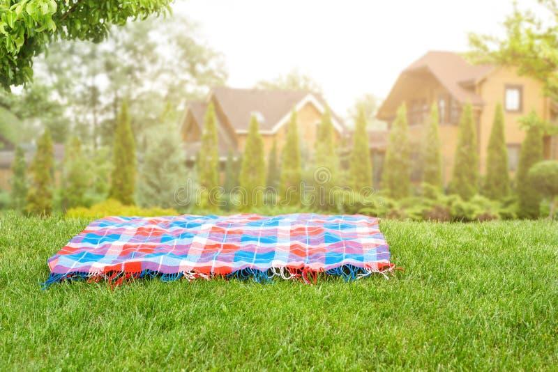 Heldere geruite mat op groen grasgazon onder bomen in tuin Vage blokhuizen op achtergrond Lege Ruimte voor stock foto's