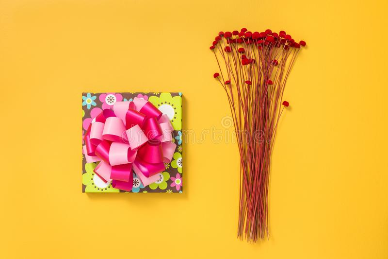 Heldere giftdoos en rode bloemen op gele achtergrond royalty-vrije stock foto
