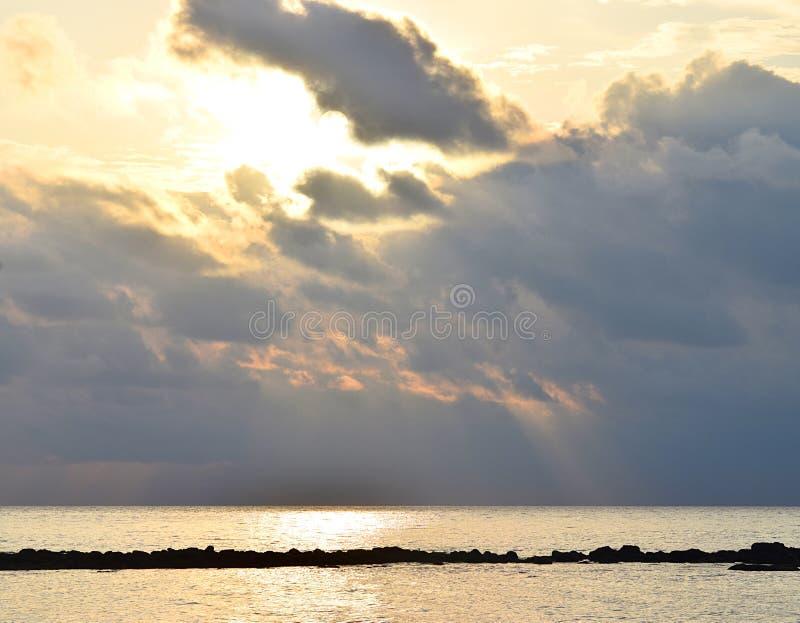Heldere Gouden Gele Zon achter Donker Grey Clouds met Warme Kleuren in Hemel en Bezinning in nog Zeewater - Neil Island, Andaman royalty-vrije stock afbeeldingen