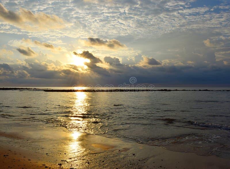 Heldere Gouden Gele Zon bij Horizon, Bewolkte Hemel, Kalm Zeewater in Sandy Beach met Weerspiegeling van Zonlicht - het eiland va stock fotografie