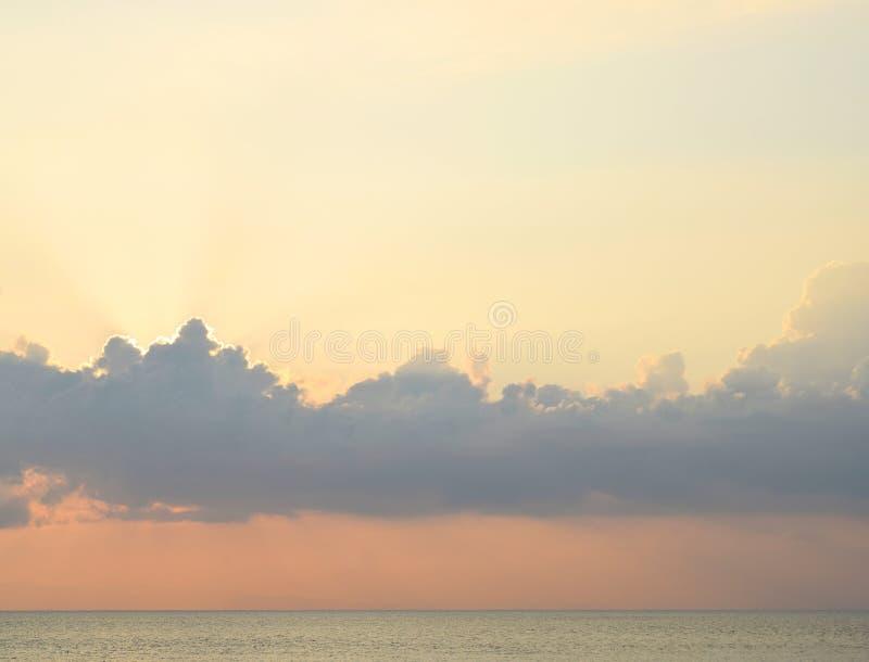 Heldere Gouden Zonnestralen door Wolken in Hemel, Blauwe Zeewater en Horizon - Natuurlijke Achtergrond stock afbeelding