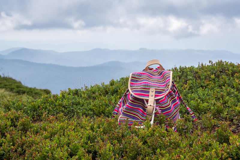 Heldere jonge meisjes` s rugzak in de bergen Het concept van de vakantie royalty-vrije stock foto's