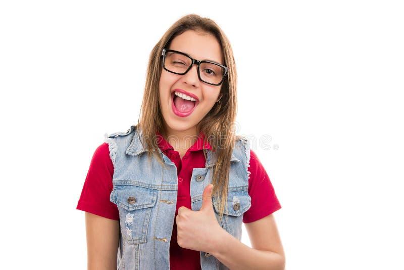 Heldere jonge vrouw die met omhoog duim knipogen stock foto