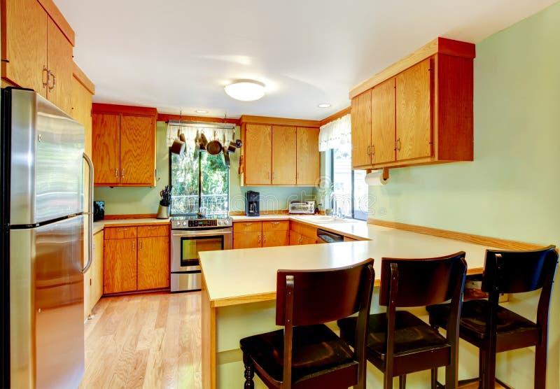 Heldere keuken met lichtbruine kabinetten en oude houten krukken