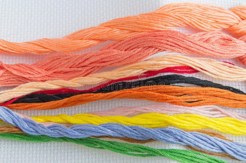 Heldere kleurrijke draad voor borduurwerkdraad op canvas Met de hand gemaakte toebehoren op witte achtergrond Plaats voor tekst,  royalty-vrije stock afbeelding
