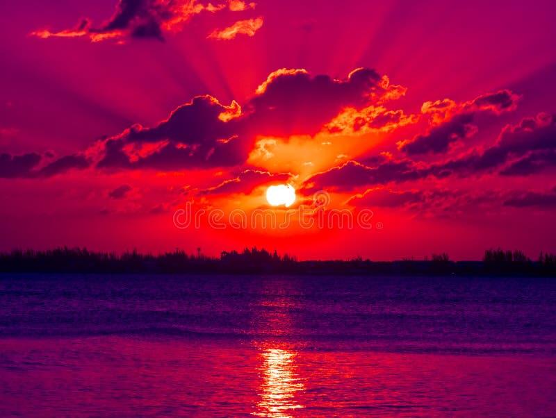 Heldere kleurrijke zonsondergang met bezinning in de oceaan stock foto's