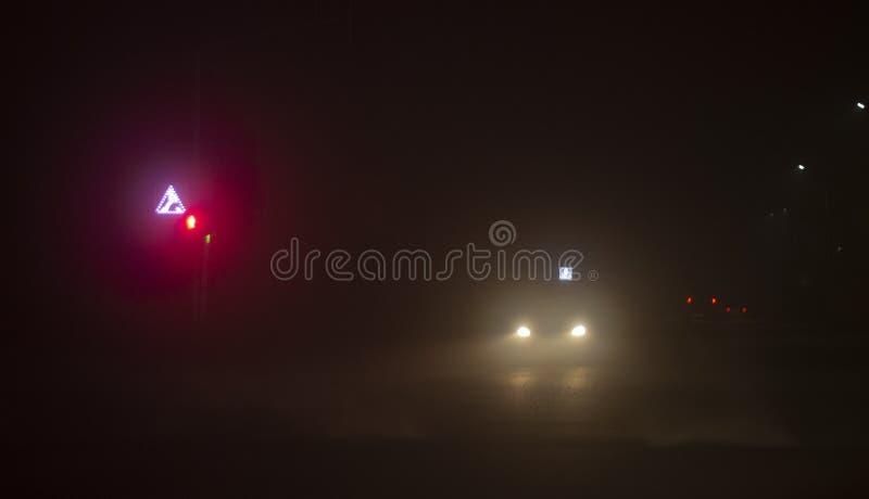 Heldere koplampen van auto het drijven op mistige weg stock afbeeldingen