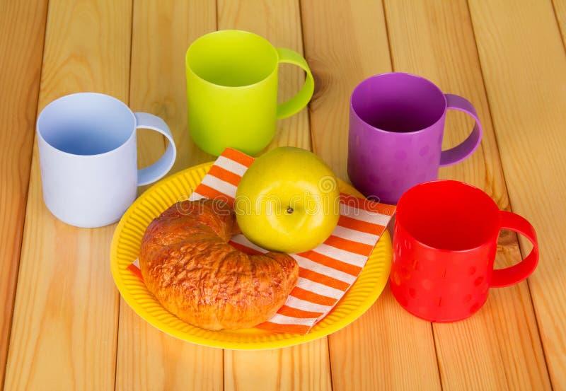 Heldere koppen en beschikbare plaat met croissant, appel stock fotografie