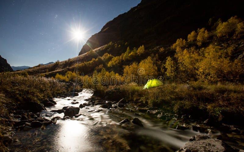 Heldere maan en verlichte tent op Baduk-rivier en vallei bij nacht royalty-vrije stock foto