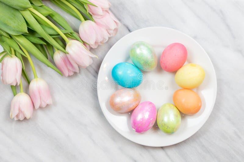 Heldere mooie de lenteachtergrond met verse tulpen en gekleurde paaseieren royalty-vrije stock afbeeldingen