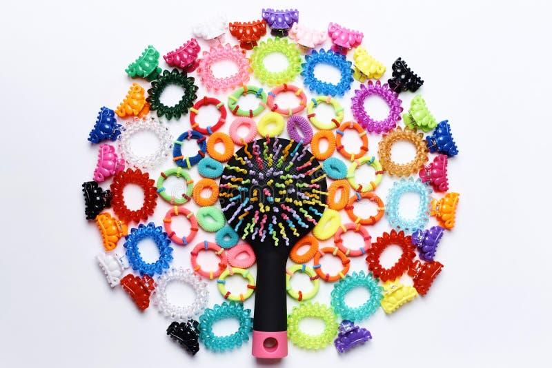 Heldere multicolored kam in een cirkel van kleine kleurrijke haarspelden en elastiekjes voor haar stock afbeelding