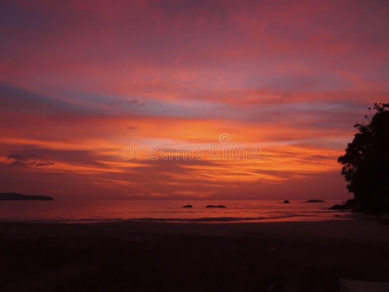 Heldere oranje, roze, purpere zonsondergangkleuren over het kalme overzees stock afbeeldingen
