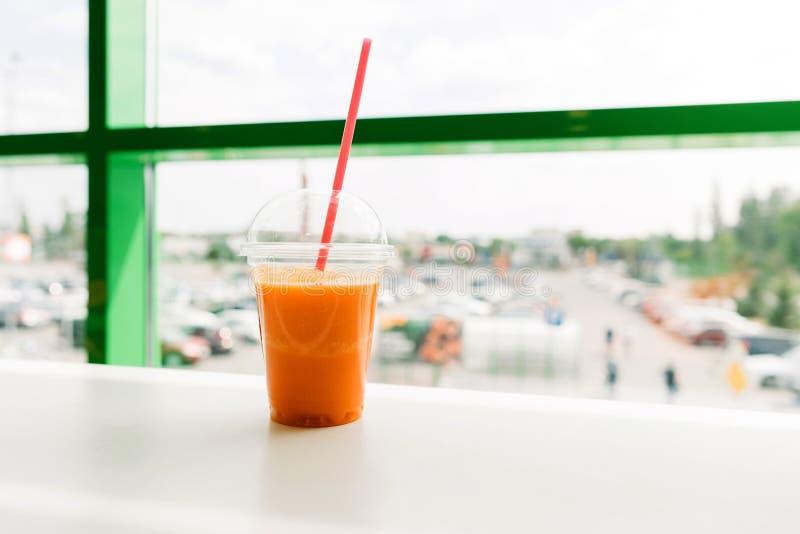 Heldere oranje wortelmandarijn smoothie in een plastic glas met stock fotografie