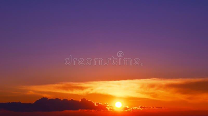 Heldere oranje zonsondergang en violette hemel stock fotografie
