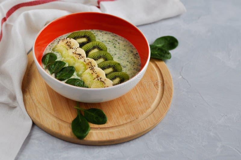 Heldere plaat met een gezonde die kom van de Ontbijtmacht van natuurlijke yoghurt, Chia-zaden, banaan, kiwi, selderie en spinazie stock afbeelding
