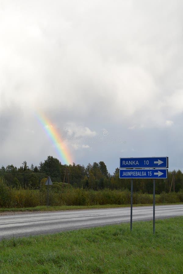 Heldere regenboog over bomen dichtbij de weg en stadsrichtingstekens royalty-vrije stock afbeeldingen