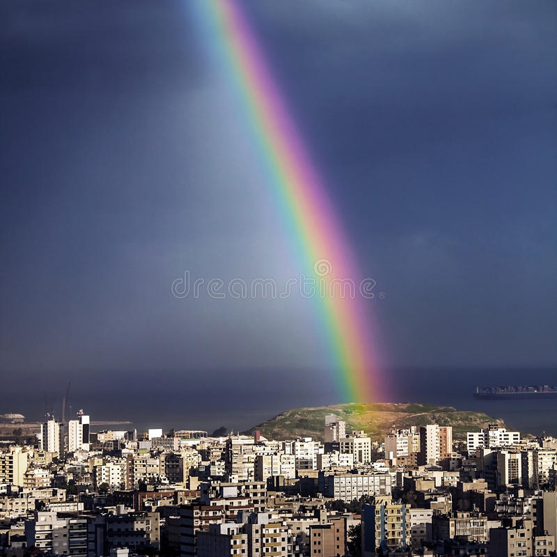 Heldere regenboog over stad stock fotografie