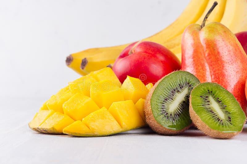 Heldere rijpe exotische vruchten van rode, gele, groene, oranje kleur met sappige gesneden plakkenmacro op witte houten achtergro stock foto