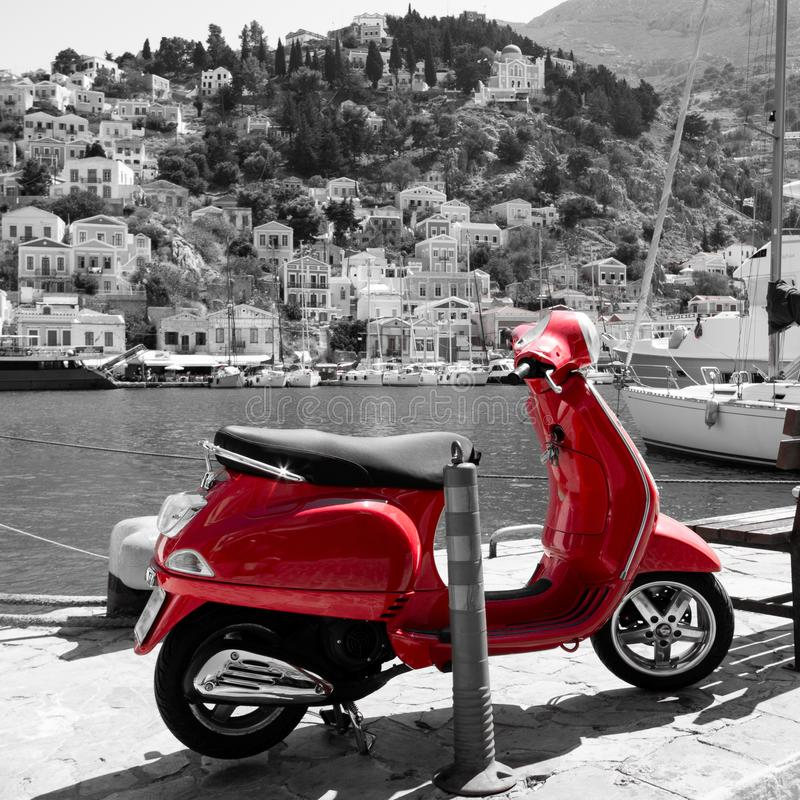 Heldere rode autoped met de haven van Symi in Griekenland in zwart-wit op de achtergrond royalty-vrije stock afbeeldingen