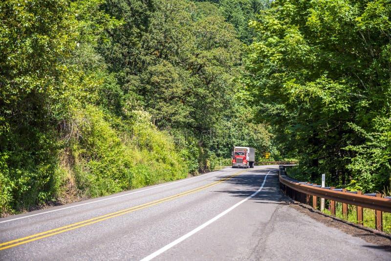 Heldere rode grote installatie semi vrachtwagen die commerciële lading vervoeren die zich op de groene bos windende weg bewegen royalty-vrije stock foto
