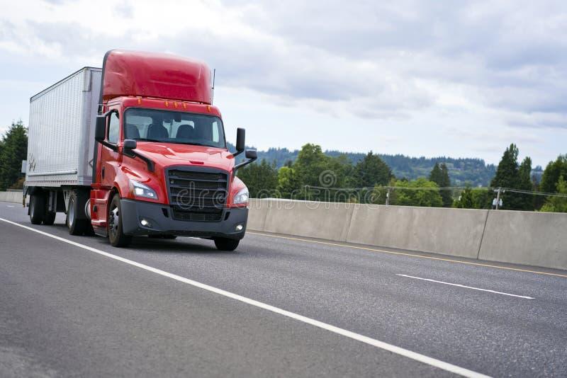 Heldere rode grote installatie semi vrachtwagen met cabinespoiler semi vervoeren royalty-vrije stock afbeelding