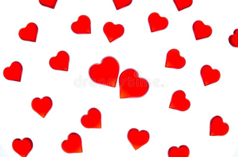 Heldere rode harten op een gestreepte achtergrond met twee rode harten Om de Dag van Valentine ` s, huwelijken, Internationale Vr stock foto's