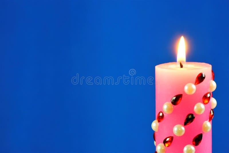 Heldere roze die kaars, op een blauwe creatieve achtergrond wordt aangestoken De kaars verlicht, en een symbool van geloof, hoop, stock afbeeldingen