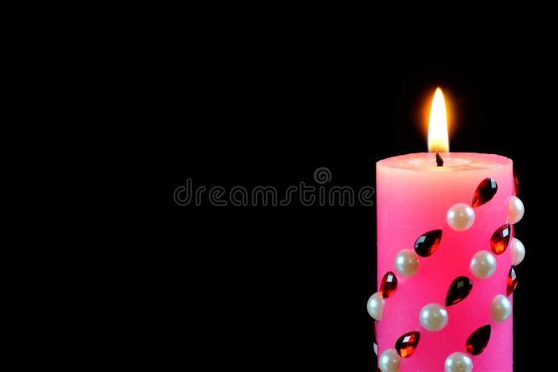 Heldere roze die kaars, op een zwarte creatieve achtergrond wordt aangestoken De kaars verlicht, en een symbool van geloof, hoop, royalty-vrije stock afbeeldingen