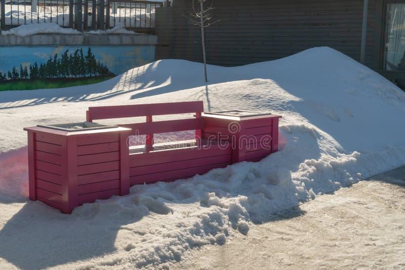 Heldere roze parkbank in de stad in de sneeuw in de winter stock afbeelding