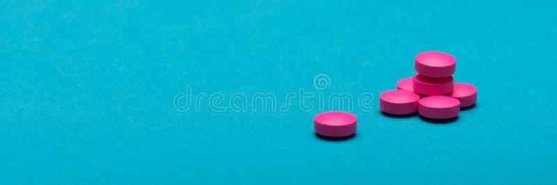 Heldere roze pillen op donkerblauwe gekleurde achtergrond Medicijn en voorschrift de banner van het pillenweb stock foto