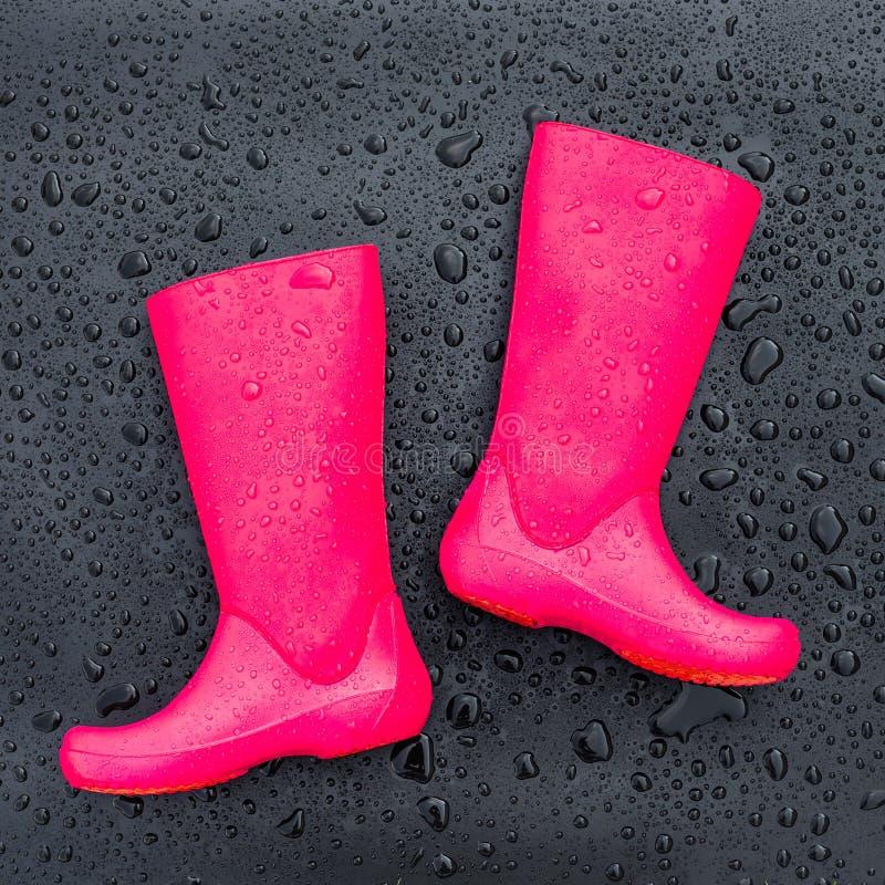 In heldere roze rubberlaarzen op zwarte natte die oppervlakte met regendruppels wordt behandeld stock afbeeldingen