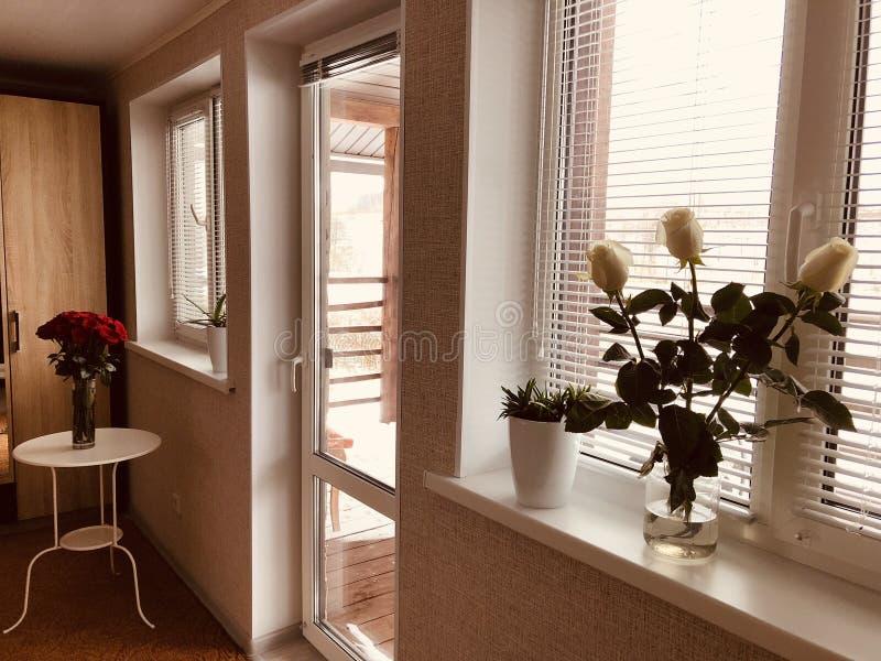 Heldere ruimte van een rustiek buitenhuis met boeketten van rozen op grote Vensters met zonneblinden royalty-vrije stock foto's