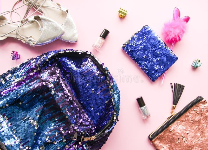 Heldere samenstelling van maniertoebehoren Schitter lovertjes kosmetische zak, kleurrijke bagpack, nagellakken, blocnote en schoe stock afbeeldingen