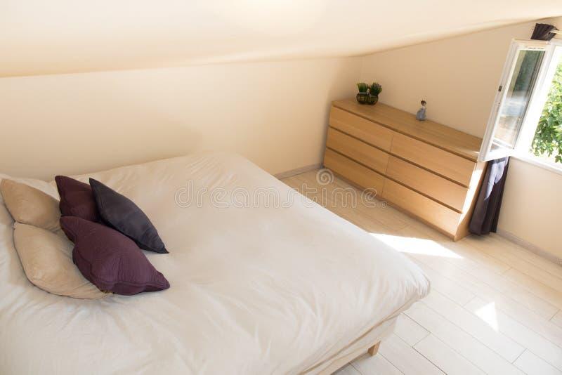 Heldere Slaapkamer in zolder met groot bed stock afbeeldingen