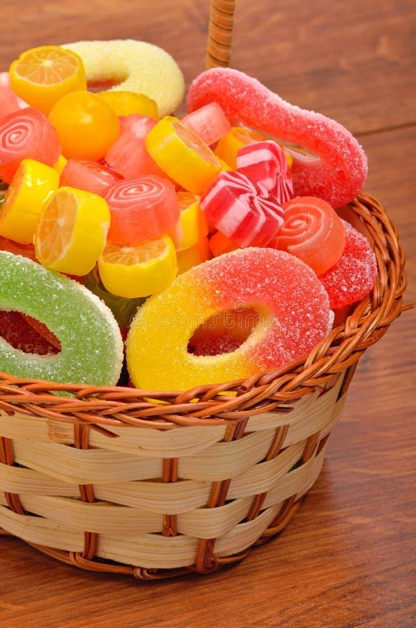 Heldere snoepjes, lollys, gelei in de rieten mand royalty-vrije stock fotografie
