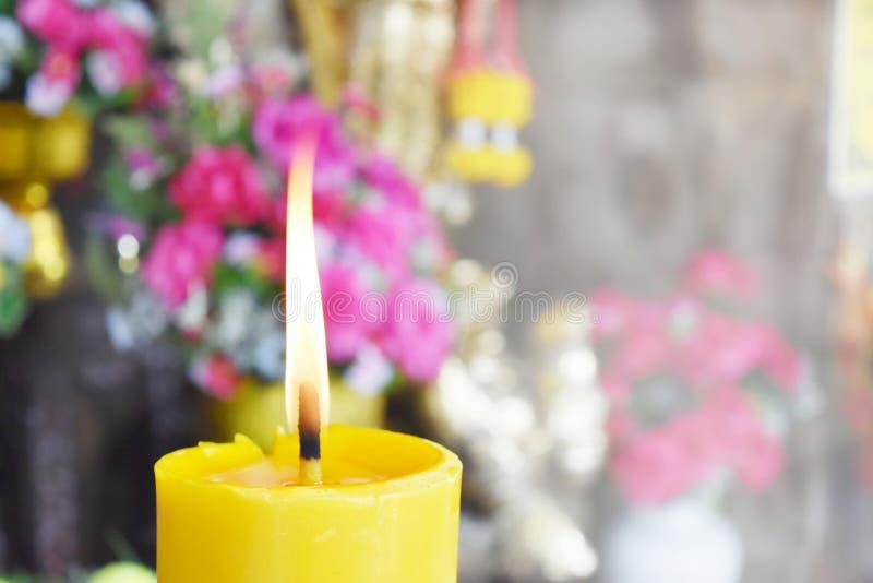 Heldere stijlachtergrond Brandende kaarsen en bloemen voor verering stock fotografie