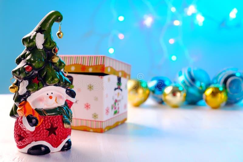 Heldere stuk speelgoed dwerg met een vrolijk gezicht en een klok op de glanzende ballen van GLB, doos op witte achtergrond stock afbeelding