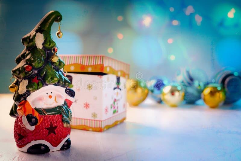 Heldere stuk speelgoed dwerg met een vrolijk gezicht en een klok op de glanzende ballen van GLB, doos op witte achtergrond stock fotografie