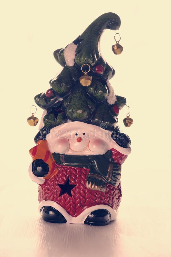 Heldere stuk speelgoed dwerg met een vrolijk gezicht en een klok op een hoed op een witte achtergrond Nieuw jaar, Kerstmisdecorat royalty-vrije stock foto
