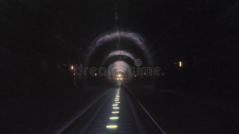 Heldere treinlichten die naar de camera komen in een donkere spoorwegtunnel royalty-vrije stock afbeelding