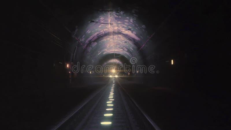Heldere treinlichten die naar de camera komen in een donkere spoorwegtunnel stock afbeeldingen