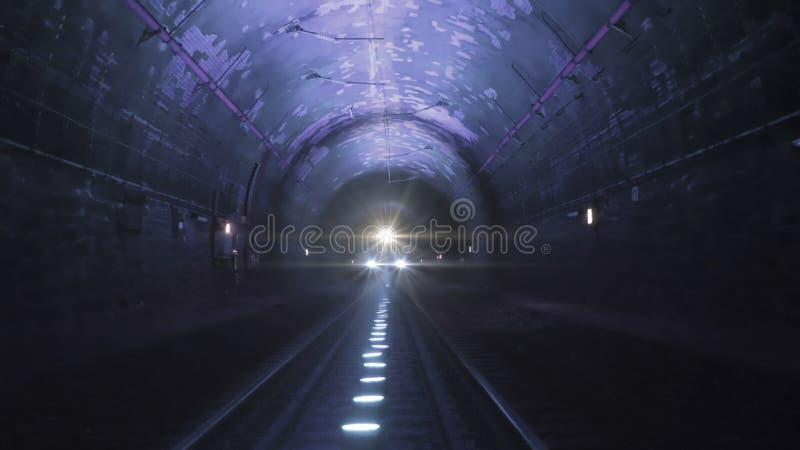 Heldere treinlichten die naar de camera komen in een donkere spoorwegtunnel stock afbeelding