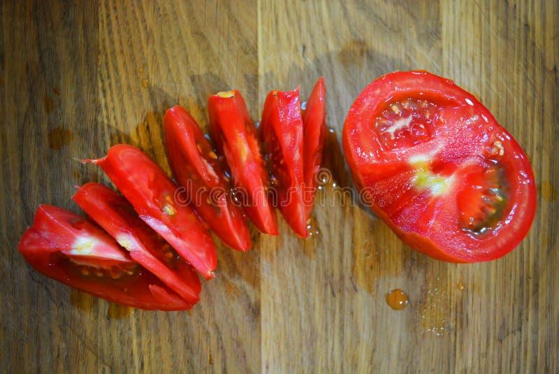 Heldere verse gesneden plakken en de helft van rode tomaat op een houten bruine chef-kokplank royalty-vrije stock foto